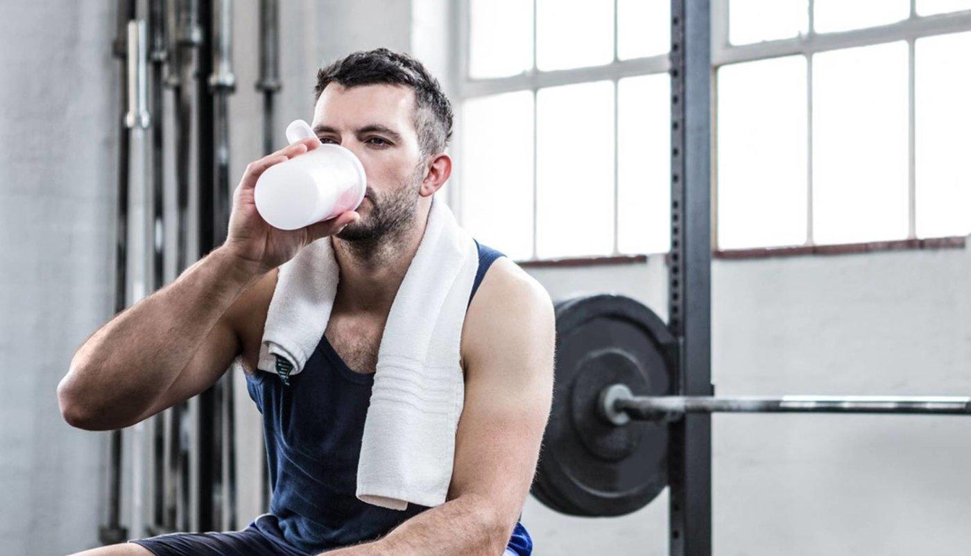 Muškarac u teretani sjedi na klupi i pije proteinski shake.