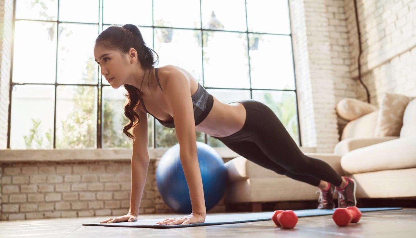 Djevojka u položaju planka na podu u svom dnevnom boravku, prirpema se na trening s bučicama kod kuće.