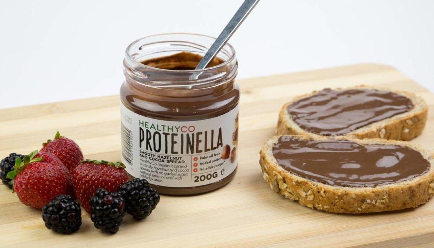 Proteinella namazana na dvije kriške kruha uz voće za doručak.