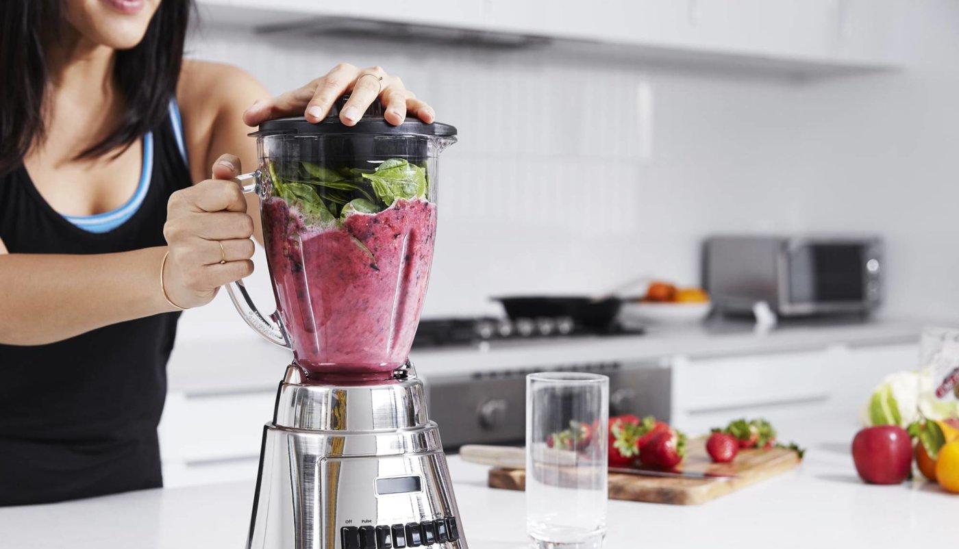 Žena radi proteinski shake u blenderu s whey proteinom i voćem.