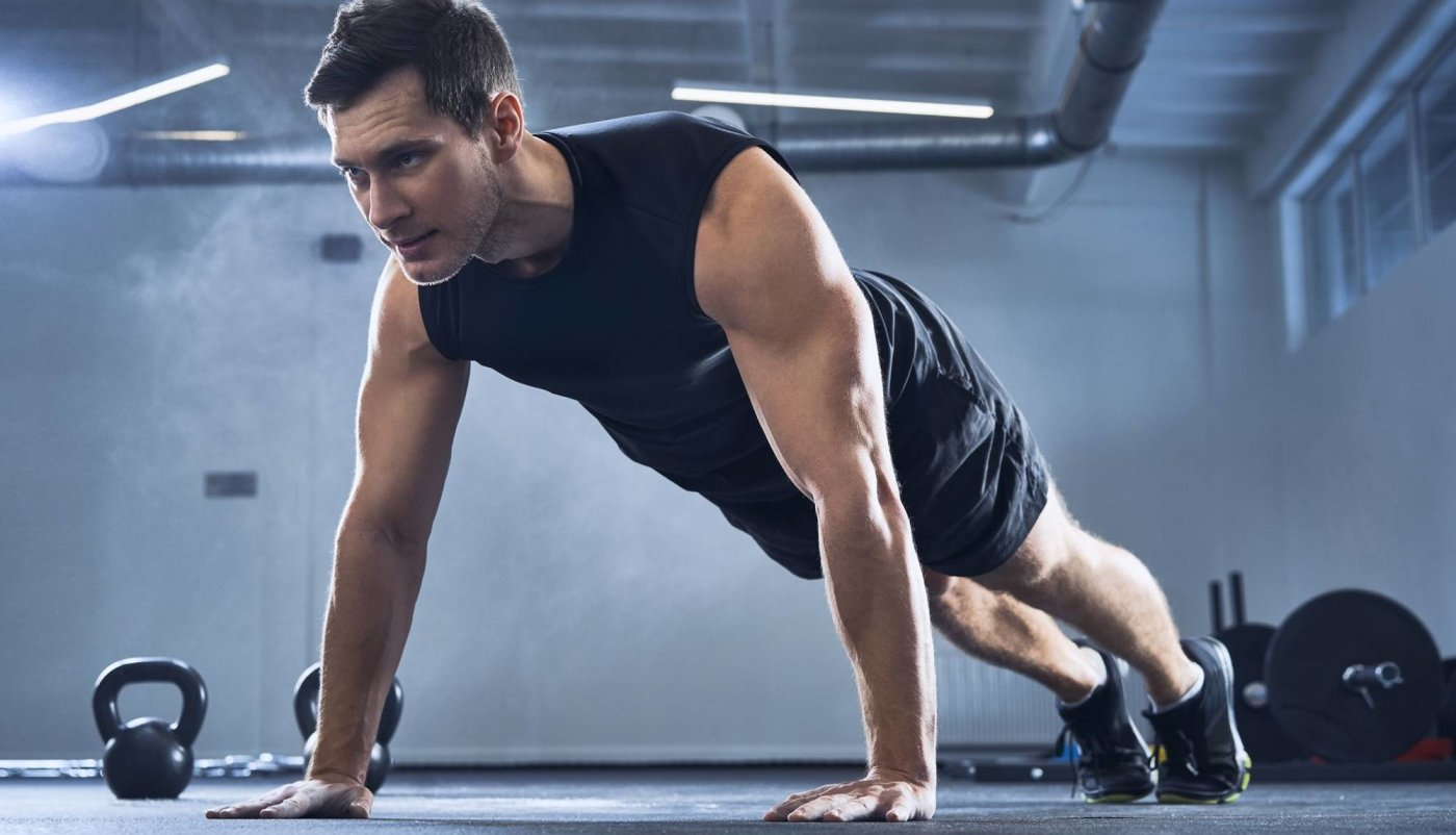 Muškarac u položaju planka na podu vježba.