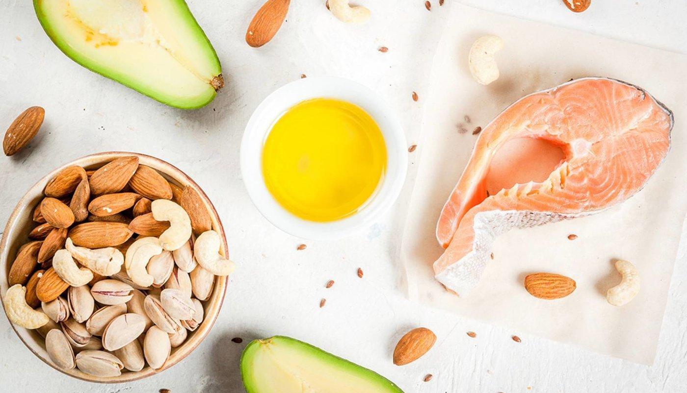 Maslinovo ulje, orasi, bademi, avokado, kesteni, omega 3 u kapsulama i losos posloženi na stolu.