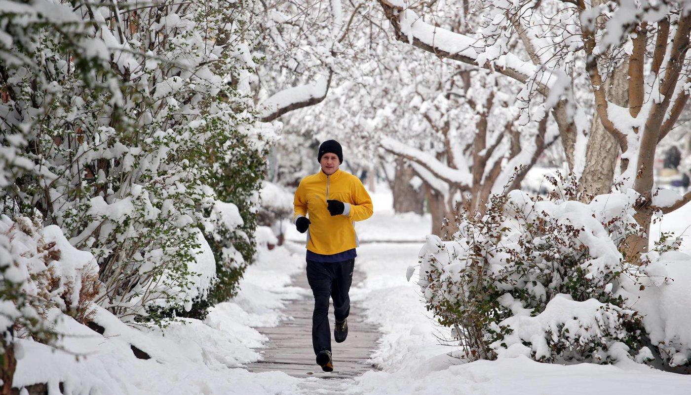 Muškarac koji trči na otvorenom po snijegu.