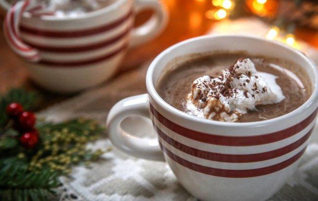 Vrući proteinski kakao u bijeloj šalici s crvenim crtama.