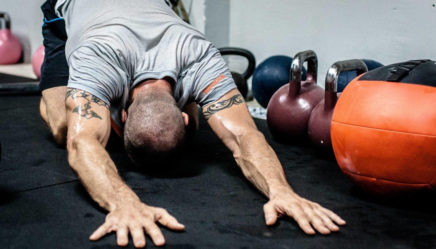 Muškarac se isteže na podu nakon treninga.