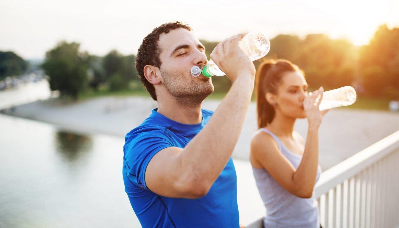 Muškarac i žena na mostu piju vodu nakon treninga.