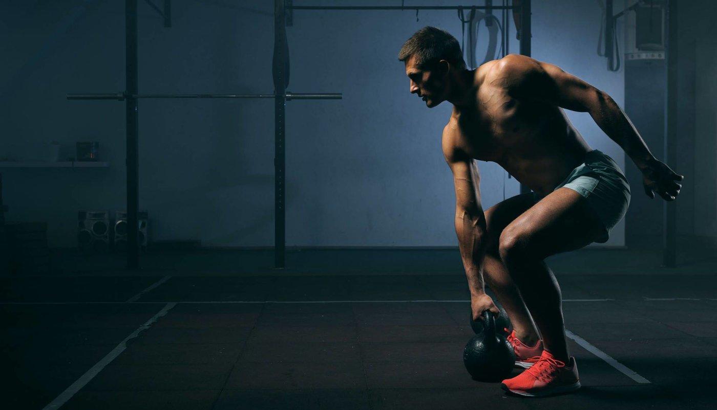 Muškarac na treningu izvodi vježbu s girjom.