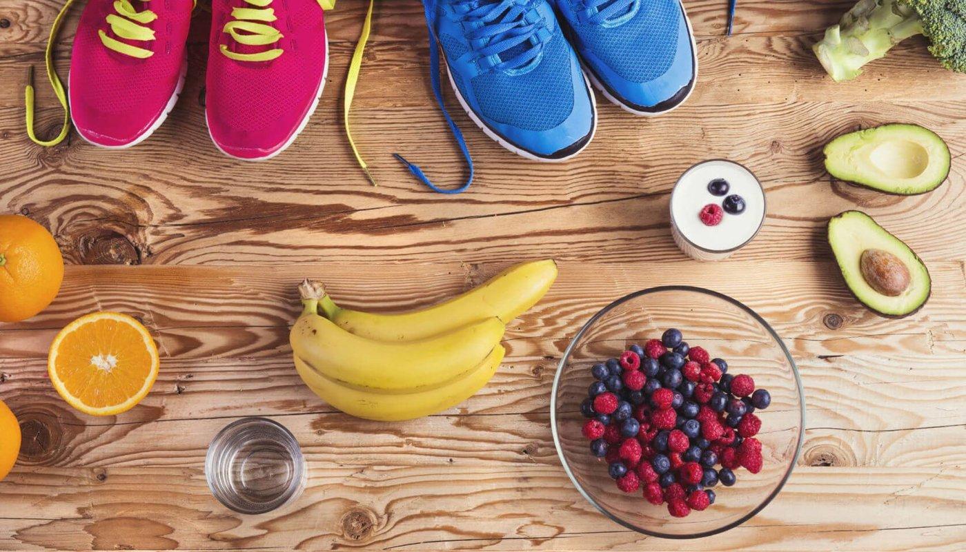 Tenisice, voće i povrće na drvenoj površini.